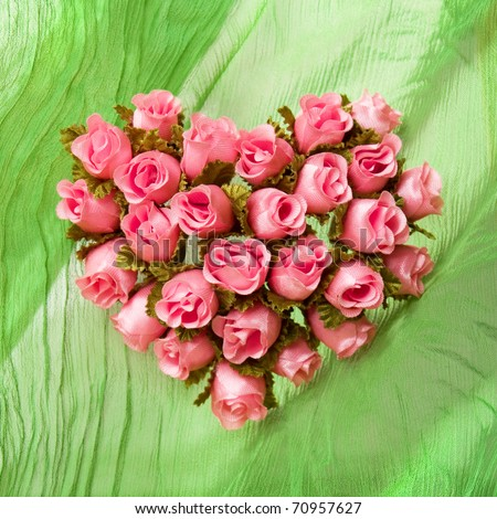 Pink rose heart on the green drapery - stock photo