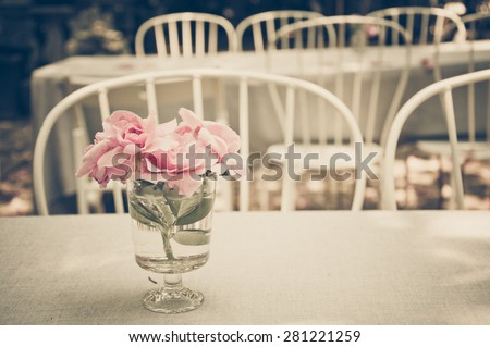 Pink rose in the glass vase on the table in the garden restaurant, vintage style - stock photo