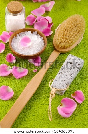 pink rose petals and salt in bowl with brush on green towel  - stock photo