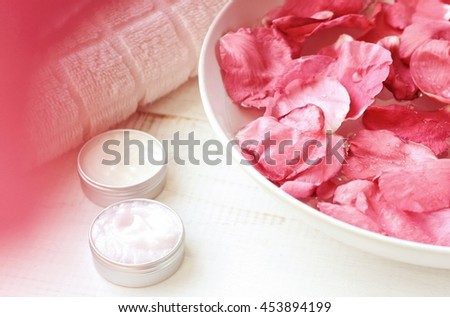 Pink rose petals in bowl, cosmetic moisturizer emollient in containers, white towel.  Pink natural blur, creamy tones. Fragrant rose flower spa.  - stock photo