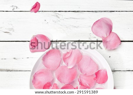 pink rose petals in bowl of water on rustic background,top view - stock photo