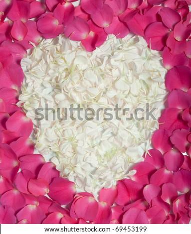 Pink rose petals surrounding cream heart as romantic symbol - stock photo