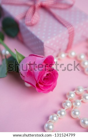 Pink rose with gift and pearls on pink surface