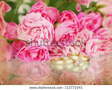 Pink roses an wedding ring on vintage background - stock photo