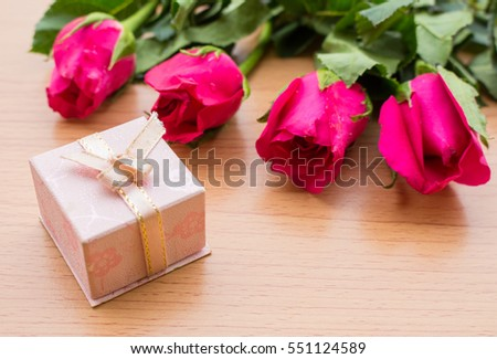 Pink roses and gift boxes on a wooden floor.