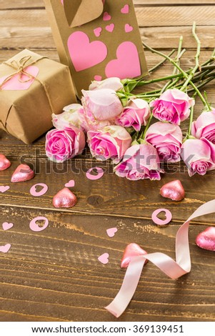 Pink roses and gift wrapped in recycled paper on rustic wood table.