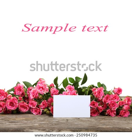 Pink roses and greeting card on a white background - stock photo