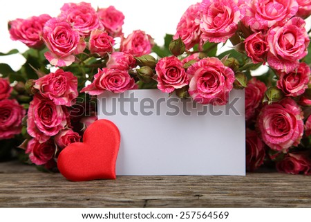 Pink roses and greeting card on a wooden background - stock photo