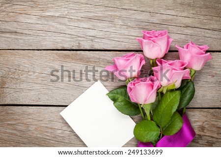 Pink roses and valentines day blank greeting card or photo frame over wooden table. Top view with copy space - stock photo