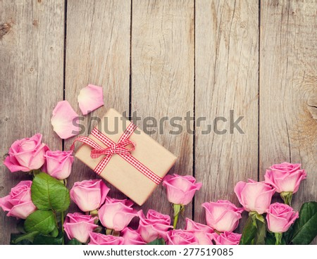Pink roses and valentines day gift box over wooden table. Top view with copy space. Toned - stock photo