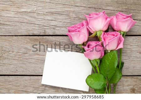 Pink roses bouquet and blank greeting card over wooden table. Top view with copy space - stock photo