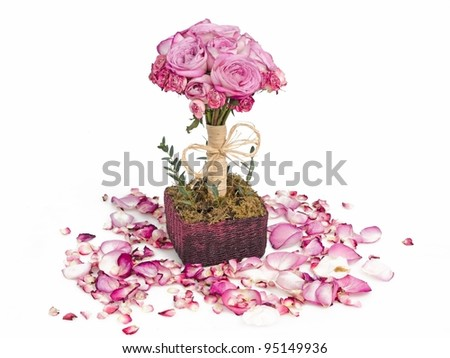 Pink roses bouquet in basket surrounded with petals - stock photo