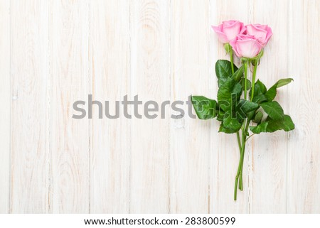 Pink roses bouquet over white wooden table. Top view with copy space - stock photo
