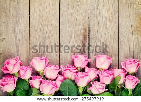 Pink roses bouquet over wooden table. Top view with copy space. Toned - stock photo