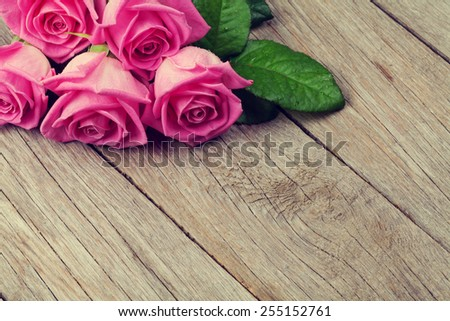 Pink roses bouquet over wooden table with copy space - stock photo