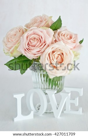 "Pink roses flowers in a vase and letters ""love"" .Floral gift for a wedding or birthday. - stock photo"