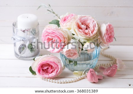 Pink roses flowers  in blue vase on white painted wooden background. Selective focus.  - stock photo