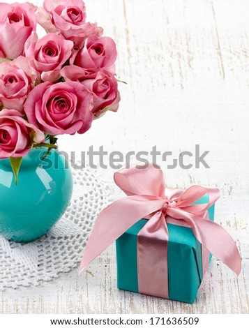 Pink roses in a vase and gift box on white wooden background - stock photo