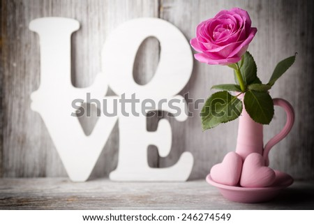 Pink roses in a vase with a Valentine's Day decoration on a wooden shelf. - stock photo