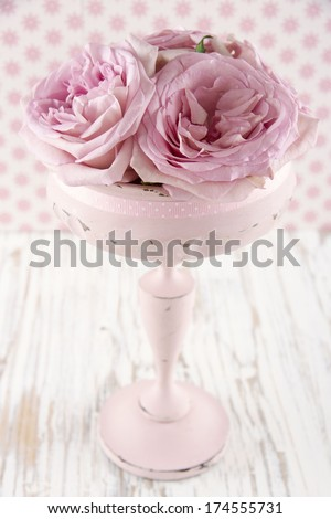 Pink roses in a wooden pastel color vase on vintage white wooden shabby chic background
