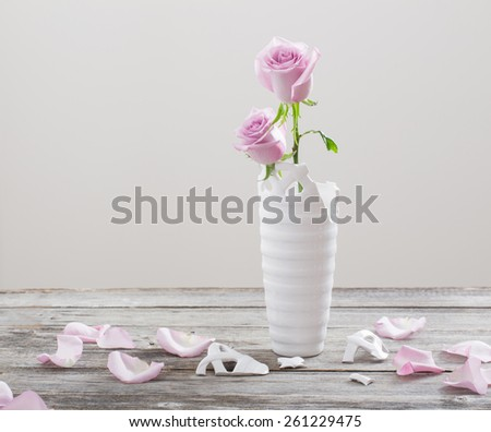 pink roses in  broken  flower vase on old wooden table - stock photo