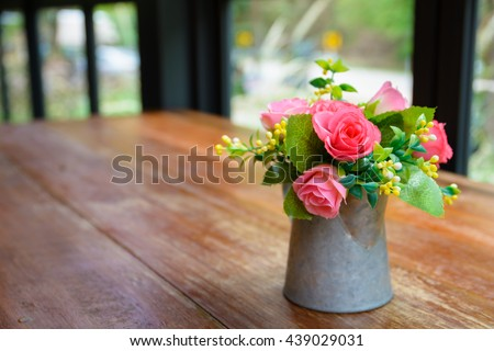 Pink roses in metal vase on wooden table by the window.