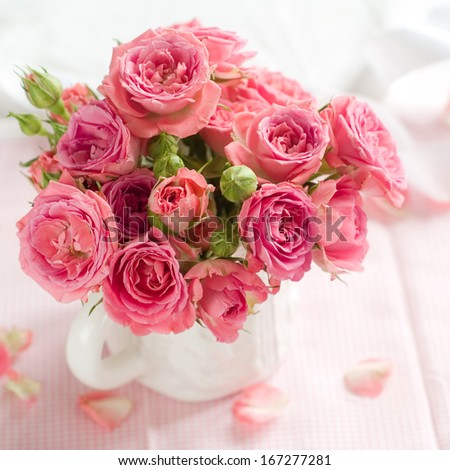 Pink roses in white cup for celebration, selective focus - stock photo