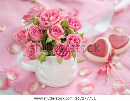 Pink roses in white cup with lollipops for celebration, selective focus - stock photo