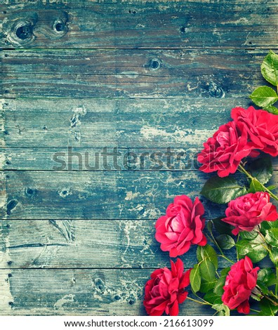 Pink roses on rustic blue wooden table. Romantic floral frame background. Valentines day concept - stock photo