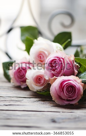 Pink roses on the wooden table, selective focus - stock photo
