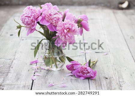 Pink roses(peony) in vase on wooden floor  - stock photo