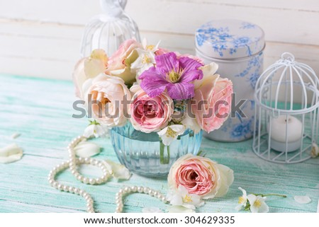 Pink roses, white jasmine and violet clematis flowers in vase  on turquoise wooden background. Selective focus.  - stock photo