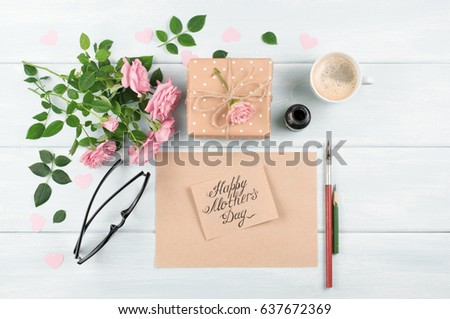 Pink roses with paper greeting card, inkwell and fountain pen, gift box and coffee cup for Mothers day on background of shabby wooden planks. Top view. Flat design.