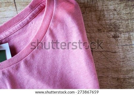 Pink round neck T-Shirt close up on wooden background - stock photo