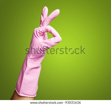 pink rubber gloves gesturing rabbit against a green background - stock photo