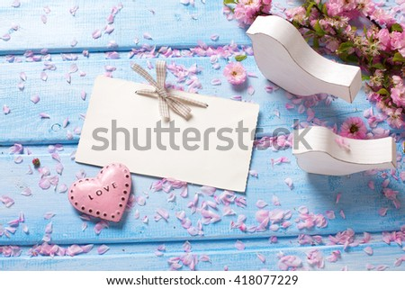 Pink  sakura flowers, empty tag, heart and two white wooden decorative birds  on blue wooden planks. Selective focus. Place for text.  - stock photo