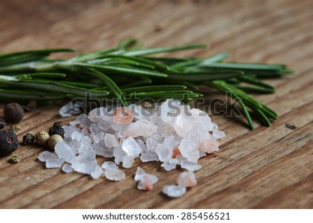 pink salt and rosemary on wooden background close up - stock photo
