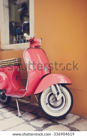 Pink scooter leaning against a wall in Italy - stock photo