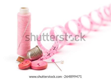 Pink sewing accessories: thread, needle, buttons, thimble and measuring tape - stock photo