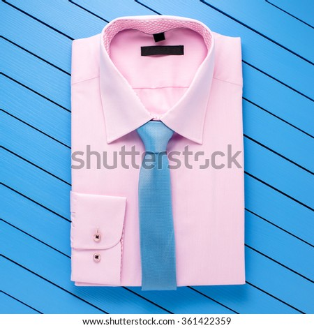 Pink shirt on blue wooden background - stock photo