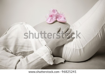 Pink shoes on mummy stomach - stock photo