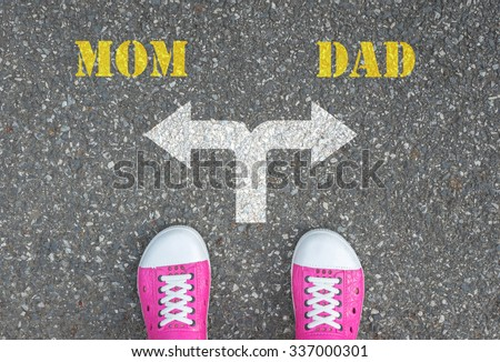 Pink shoes standing at the crossroad - mom or dad - stock photo