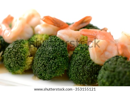 Pink shrimp fried with broccoli on white dish
