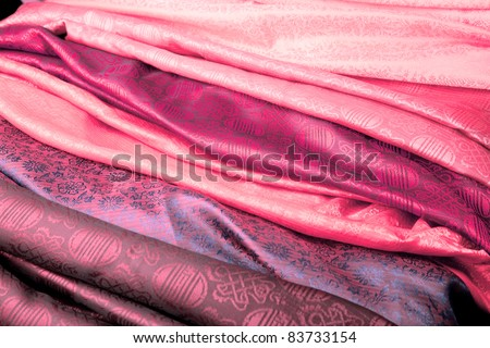 Pink silk fabric from India in a stack. - stock photo