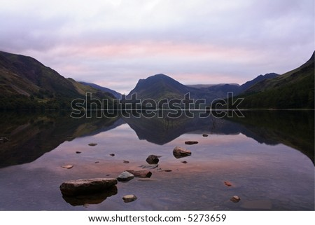 Pink skies before sunrise over Lake Buttermere. - stock photo