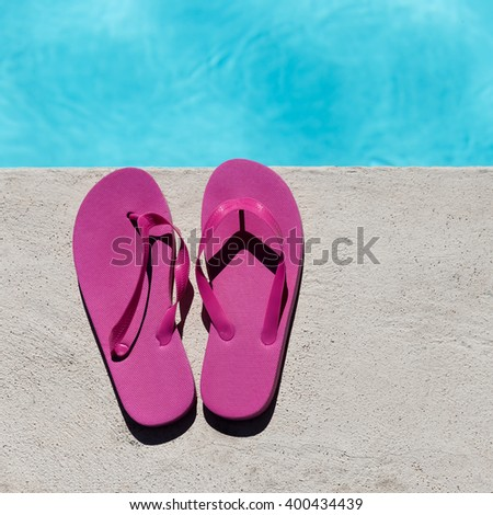 Pink slippers near swimming pool at poolside