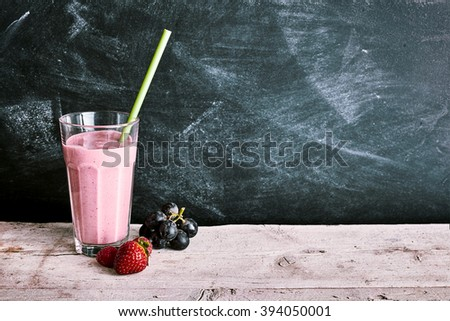 Pink smoothie drink in tall glass next to whole grapes and strawberries over wooden table and black background with copy space - stock photo
