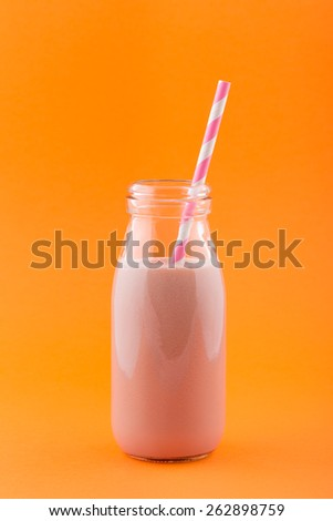Pink Smoothie in a Retro Milk Bottle with Striped Drinking Straw on a Orange Background. - stock photo
