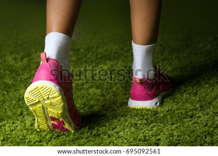 Pink sneakers on the legs of a woman on the grass