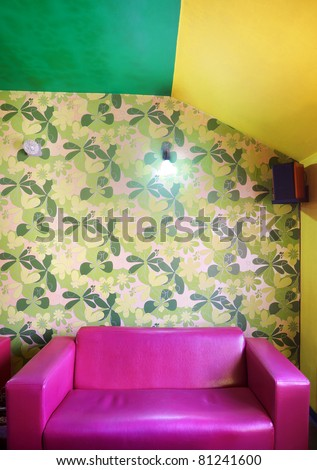Pink sofa in front of a wall with flower wallpapers. - stock photo
